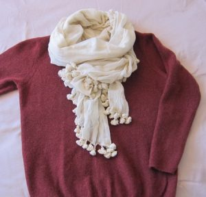 ワインレッドのセーターとポンポンストール